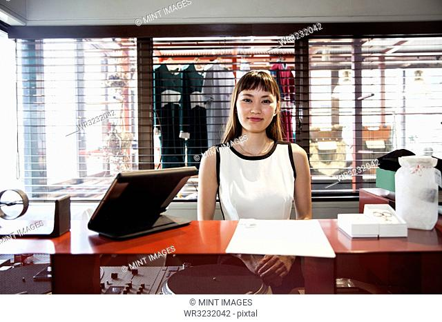 Smiling Japanese saleswoman standing at a counter in clothing store