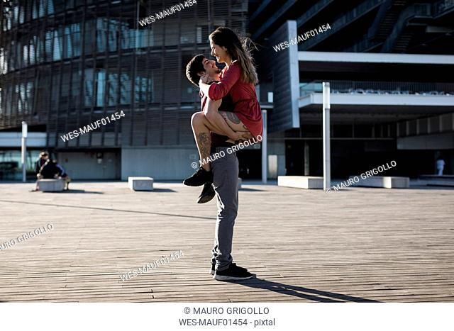 Young man lifting up happy girlfriend on city square