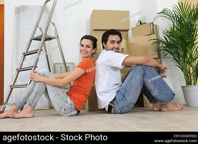 Couple sitting back to back next to step ladder