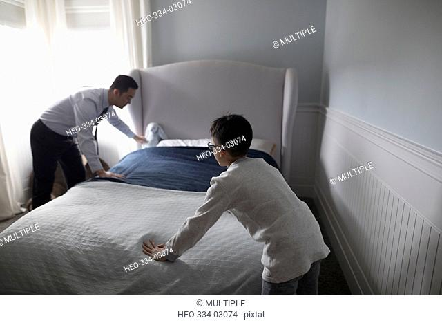Father and son making bed in bedroom