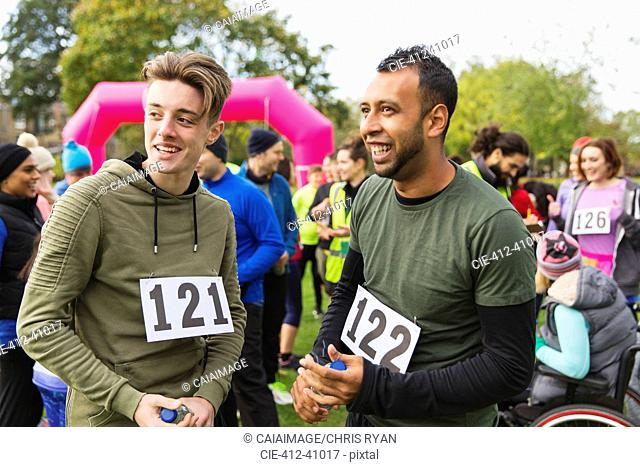 Male runners talking after charity run in park