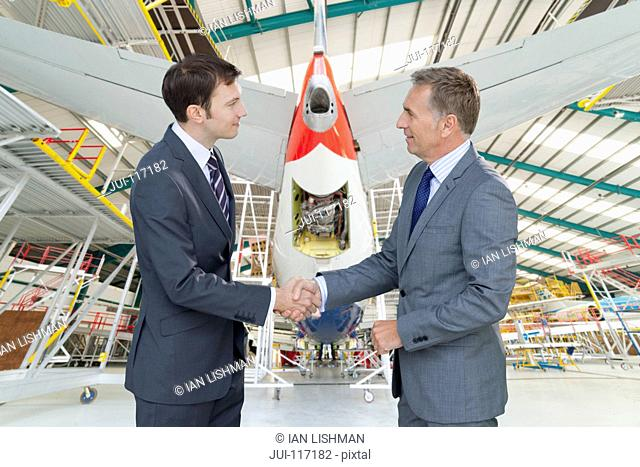 Businessmen Shaking Hands In Aircraft Maintenance Hangar