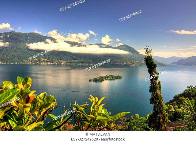 Alpine lake with island and blue sky with clouds