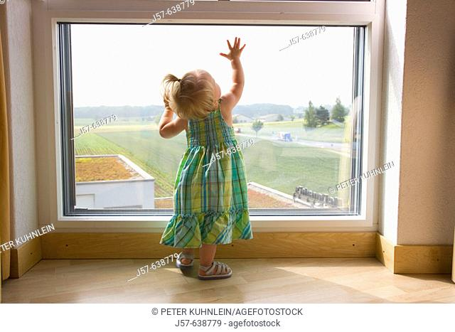 16 month old girl playing at a window in a hotel room overlooking a field and highway