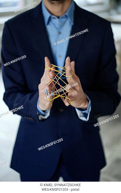 Close-up of businessman holding rubber bands