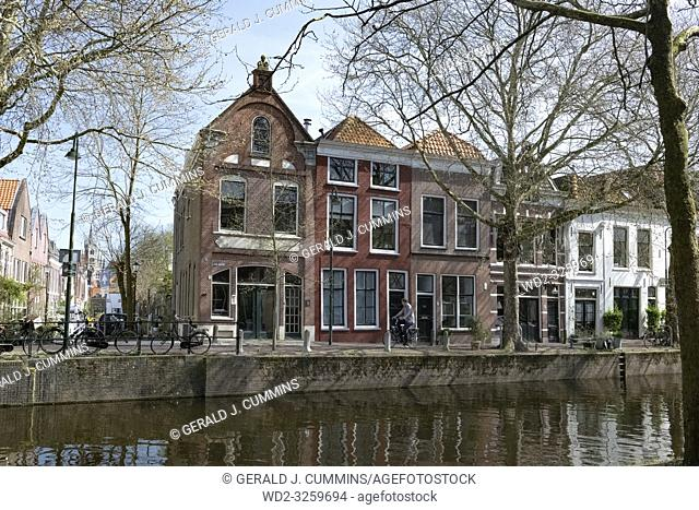 Netherlands, Gouda, 2017, cyclist passing in front of traditional houses on the banks of a canel