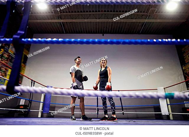 Young male and female boxers standing in boxing ring