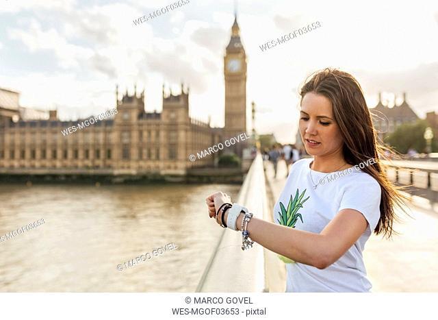 UK, London, oman using her smartwatch on Westminster Bridge