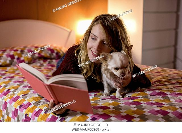 Smiling woman lying on bed with her dog reading a book