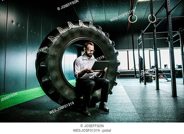 Businessman sitting in truck tire in a gym, using laptop