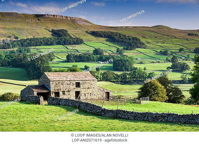 A stone barn set amidst beautiful rolling countryside backed by Abbotside Common near Hawes in the Yorkshire Dales