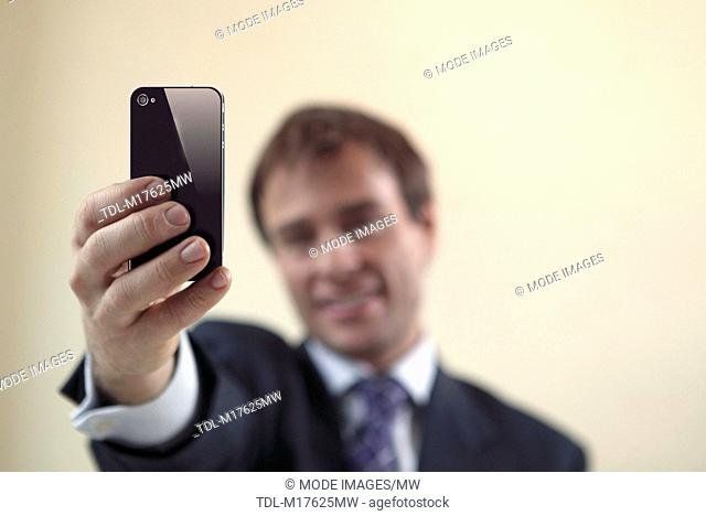 A businessman taking a photograph of himself using a smartphone