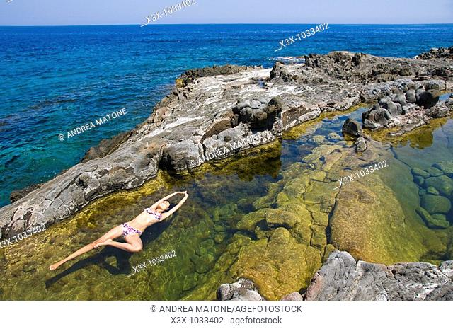 Woman floating in colorful water pool by the sea  Pantelleria Island, Sicily, Italy