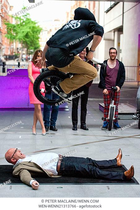 Chris Evans and Alex Jones, The One Show presenters watch on as a uni-cyclist bunny hops over Greg Wallace, presenter of Masterchef at Broadcasting House