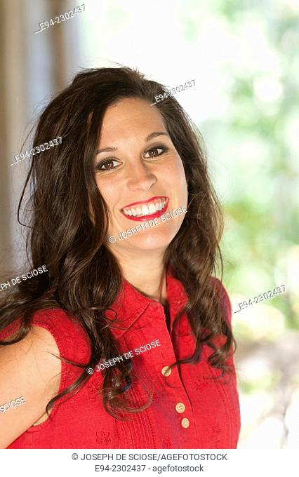 A portrait of a smiling 36 year old brunette woman looking directly at the camera, outdoors.s