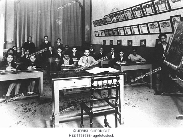 Classroom at Rosh Pinna School, Libya, c1933? The walls are covered with awards won by the Maccabi sports teams. The Maccabi Movement began in 1895 with the...