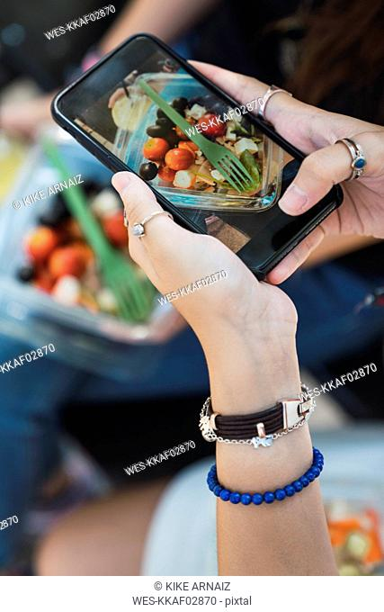 Girl taking pictures of a salad witz her smartphone, close up