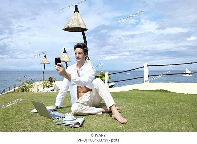 A man sitting on grass and working on a laptop
