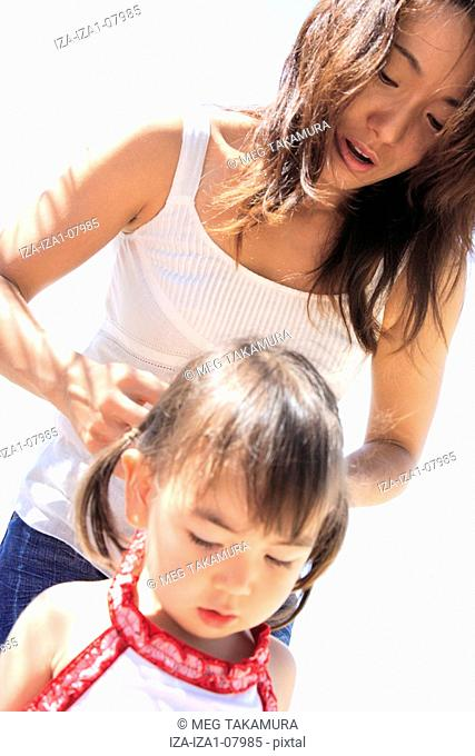 Close-up of a mid adult woman adjusting hair of her daughter