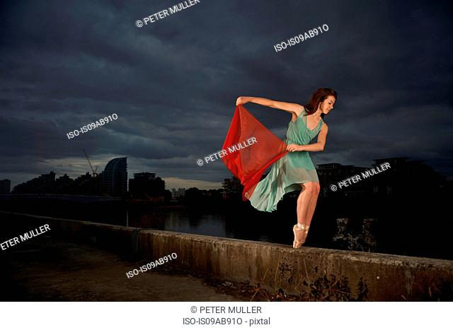 Ballet dancer holding red scarf on wall