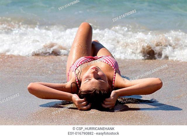 Beautiful young girl sunbathing on sand