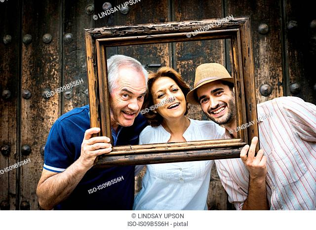 Portrait of adult family, holding wooden frame in front of their faces, Mexico City, Mexico