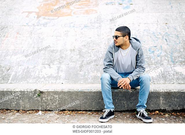 Young man sitting on a wall wearing a hoodie