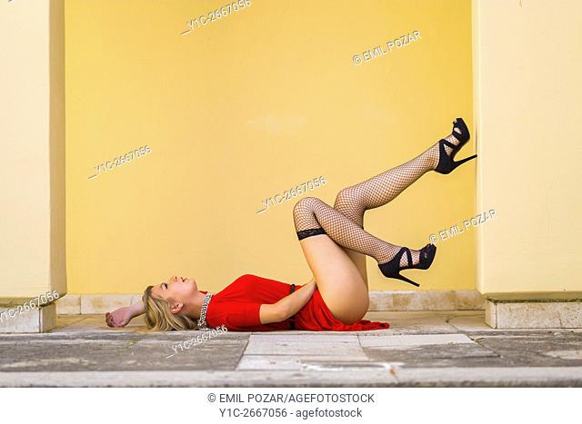Pretty young woman lying on her back on street