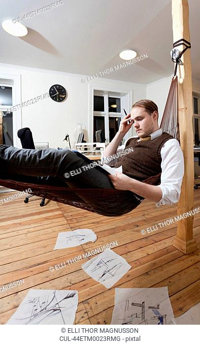 Businessman taking notes in hammock