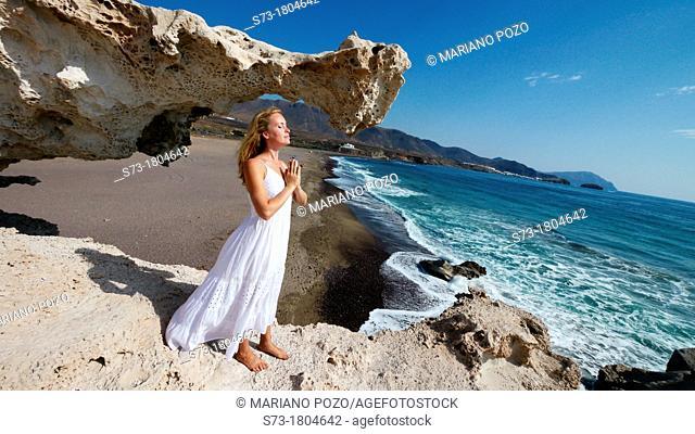 Woman meditating in Playa del Arco, Los Escullos Natural Reserve of Cabo de Gata-Níjar, Almería province