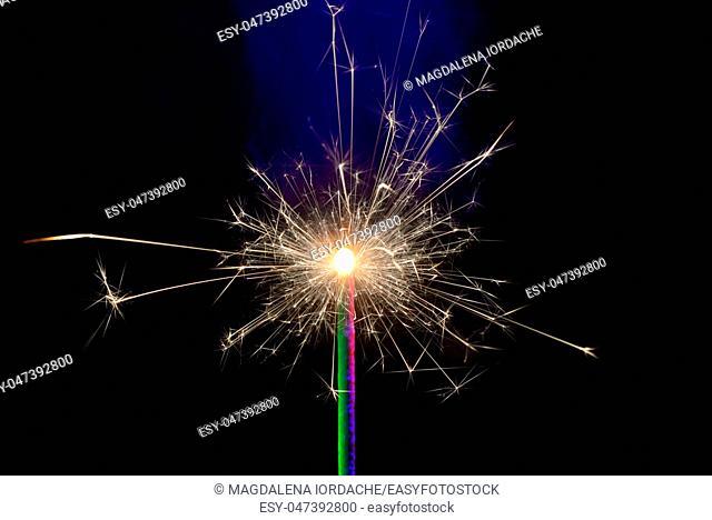 Burning sparkler isolated on black background
