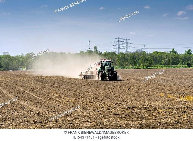 Agricultural landscape with a tractor ploughing a field, trees and overhead powerlines, Heidenau, Saxony, Germany