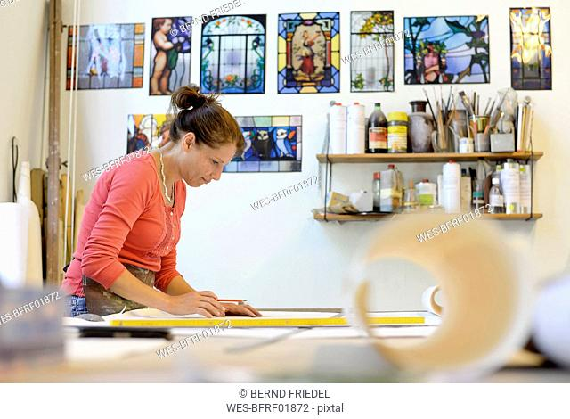 Woman working on draft in glazier's workshop