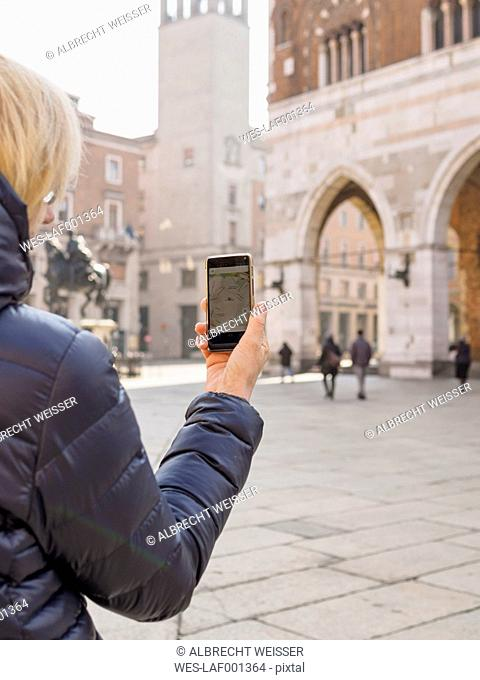 Italy, Piacenza, female tourist with smartphone at Piazza Cavalli