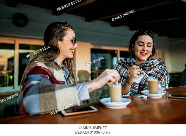 Two young women having coffee at outside cafe
