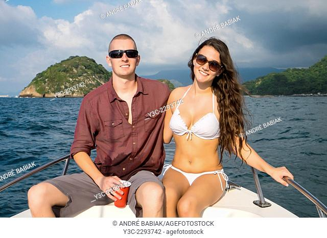 Young couple smiling at camera while on a private boat tour to Los Arcos National Marine Park, Pacific Ocean, Banderas Bay, Mexico