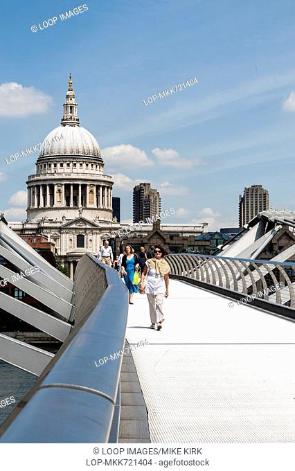 Tourists walking over the Millennium Bridge with St Paul's Cathedral in background