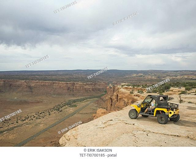 People in off-road vehicle at edge of cliff