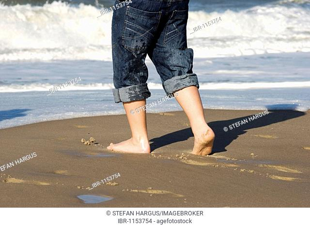 Legs of a boy on the shore of the North Sea coast of Holme Land, Jutland, Denmark, Europe