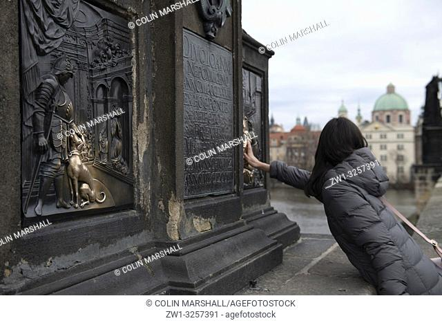 Woman touching religious icon of bronze bas-relief of King Wenceslas with dog under statue of St John of Nepomuk for luck, Charles Bridge, Prague