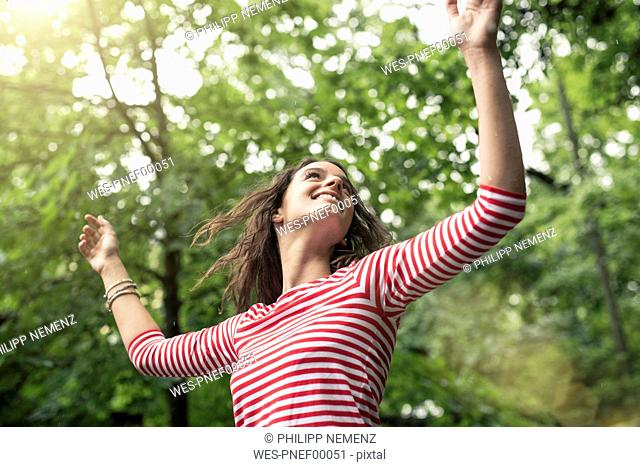 Happy young woman with raised arms dancing in nature