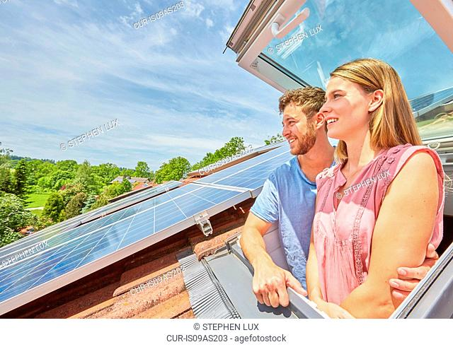 Young couple looking out of window of solar panelled roof
