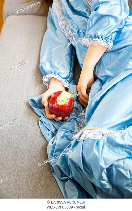 Little girl dressed up as a princess holding bitten red apple, partial view