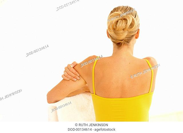 Back view of woman wearing yellow vest, resting left arm on white towel, right arm massaging left upper arm