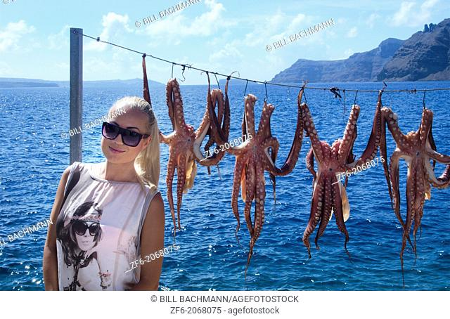 Greece Santorini Oia Cyclades Greek Islands fishing village with Europen woman tourist below Oia with octapus squid hanging on rope Greek; Islands; beautiful;...