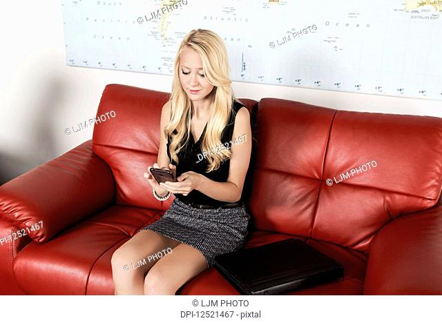 A beautiful young millennial business woman with long blond hair using her smart phone in the lobby of a workplace while waiting for a job interview; Sherwood...