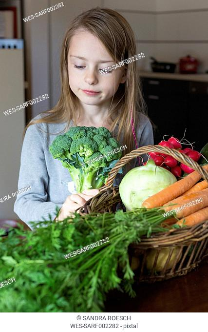 Portrait of girl with wickerbasket of fresh vegetables looking at broccoli