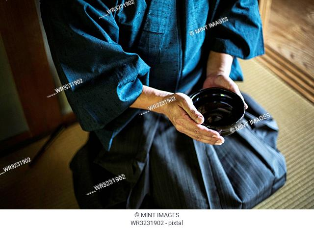 High angle close up of Japanese man wearing kimono holding tea bowl during tea ceremony