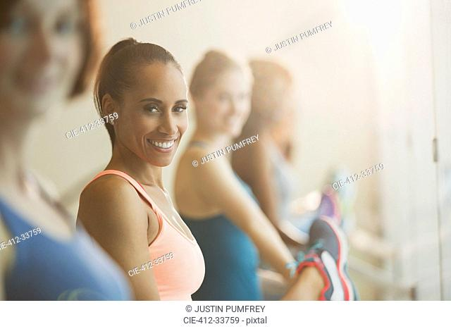 Portrait smiling women stretching legs at barre in exercise class gym studio