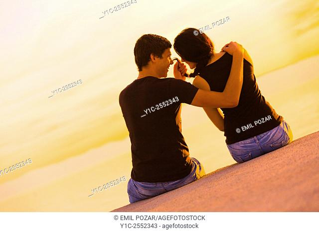 Playful teen couple before sunset horizon